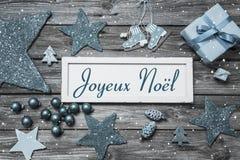 Wesoło kartka bożonarodzeniowa w błękitnym i białym z francuskim tekstem na woode obraz stock