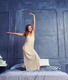 Wesoło kobieta w długiej koszula nocnej pozyci z nastroszoną ręką na th Obraz Royalty Free