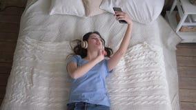 Wesoło kobieta w hełmofony cieszy się muzykę i bierze selfie fotografię na telefonie komórkowym podczas gdy relaksujący na zbiory