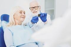 Wesoło męski dentysta wyjaśnia główną sprawę obraz stock