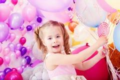 Wesoło mała dziewczynka pozuje z wiązką balony zdjęcia stock