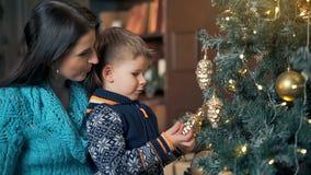 wesoło szczęśliwi Boże Narodzenie wakacje Mama i syn dekoruje choinki indoors zdjęcie wideo