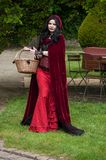 Portrait of woman with little Red Riding Hood costume  posing in park at cosplay exhibition event stock photo