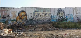 West Bank barrier with murals of Palestinian leaders. Imprisoned Marwan Barghouti and late Yasser Arafat, painted on Palestinian-Israeli separation wall at stock photo