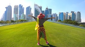 West Bay corniche woman. Travel in Qatar. Happy woman with sunhat in a park along Corniche promenade at sunset. West Bay skyline on background. Tourist enjoys in stock footage