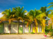 West Bay Rd-Colorful Empty Flats Building. Grand Cayman, Cayman Islands, vacant apartment building, Caribbean-style, shaded by palm trees stock images