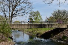 West Bridge. This is a Spring picture of the cyclist crossing the West Bridge over the DuPage River in the Morton Arboretum located in Listless, Illinois.  This Stock Images