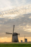 Three windmills on a cloudy evening in Netherlands. Stock Images