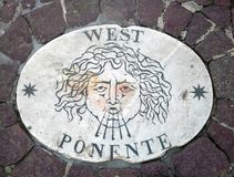 West - a head symbolizing the direction of the wind. An ancient image on a marble slab in St. Peter`s Square in the Vatican. Europ. E. Italy. Rome. Compass`s royalty free stock photos