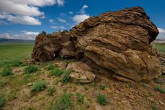 Lonely rocks of the boundless steppe. West Kazakhstan. In the boundless steppe there is a lonely mountain complex Shirkala, which from a distance looks like a royalty free stock image