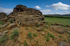 Lonely rocks of the boundless steppe. West Kazakhstan. In the boundless steppe there is a lonely mountain complex Shirkala, which from a distance looks like a stock photography