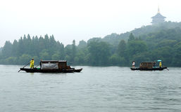 West Lake in March. March West Lake Amidst the Rain, boatmen on the lake leisurely rocked the boat, the boat in the middle of the lake dangling drift Royalty Free Stock Photo