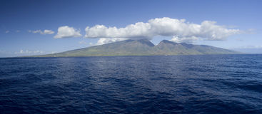 West Maui Lahaina Coast Panorama. West Maui Lahaina Coast taken from the ocean .  Billowing cumulus clouds above island and ocean in the foreground Royalty Free Stock Photography
