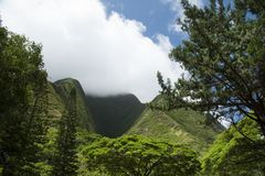West Maui Mountains Rise Into Clouds. West Maui Mountains in the Ioa Valley reach into the clouds. Maui is one of many popular Hawaiian tourist destinations stock images