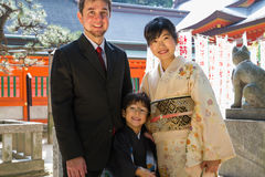 West Meets East for 7-5-3. An international couple, White and Japanese, pose with their child in suit and kimono in front of a shrine for a 7-5-3 Ceremony, a Royalty Free Stock Images