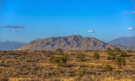 West Mountain against a brilliant blue sky in Utah. Scenic view of West Mountain in Utah with a brilliant blue sky in the background. A vast terrain with royalty free stock photography
