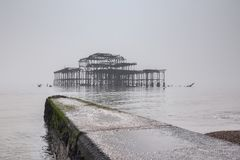 West Pier Brighton UK. Brighton Beach and the remains of the old West Pier on a foggy day in flat light, Sussex, England, UK royalty free stock photo
