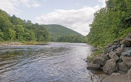 West River. Rocks, shoreline and Green Mountains National Forest looking south, West Dummerston Vermont in Summer royalty free stock photography
