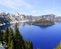 West side of Crater Lake. Wizard Island in the crystal clear blue waters of Crater Lake in Crater Lake National Park in Oregon Stock Photography