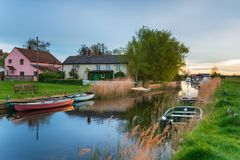 West Somerton on the Norfolk Broads. Evening light over boats moored by pretty cottages at West Somerton on the Norfolk Broads stock photography