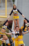 West Virginia University Cheerleaders - Stunt. MORGANTOWN, WV - OCTOBER 23: Members of the West Virginia University cheerleading squad perform on the field prior royalty free stock photo