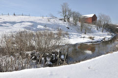 West Virginia Winter Red Barn. Beautiful winter scene in Canaan Valley, West Virginia with a red barn reflected in a cold creek Royalty Free Stock Image