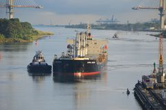Westbound Container Ship Entering Gatun Locks. West bound container ship being guided by a Canal Authority tugboat while preparing to enter the Gatun Locks on Stock Photo
