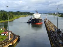 Westbound Tanker Entering the Panama Canal. A westbound oil tanker assisted by two tug boats approaching the first atlantic lock on the panama canal Royalty Free Stock Photography
