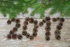 Westchnienie symbol od sosnowych rożków liczy 2017 na starego retro rocznika drewnianym tle Fotografia Stock