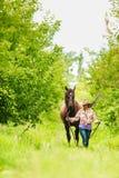 Westcowgirlfrau mit Pferd Ein Radfahrer- oder Radfahrerreiten entlang einem konkreten Fahrradweg Lizenzfreies Stockbild