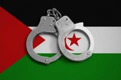 Westelijke de vlag en de politiehandcuffs van de Sahara Het concept naleving van de wet in het land en bescherming tegen misdaad royalty-vrije stock afbeelding