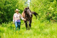 Westelijke veedrijfstervrouw met paard Fietser of fietser het berijden langs een concreet fietspad Stock Foto's