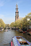 Westerkerk, Amsterdam. Amsterdam canal with tour boats and the tower of the Westerchurch in the background royalty free stock image