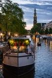 Westerkerk y casa flotante en la puesta del sol en Amsterdam Foto de archivo