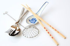 Western and Asian eating tools. A variety of Western and Asian eating tools like a metal fork and an spoon, wooden chopsticks, a chinese ceramic spoon and a Royalty Free Stock Image