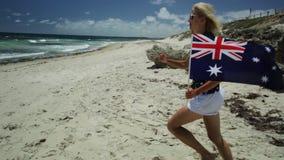 Western Australia Running flag. Close up of woman running on white beach waving Australian Flag. Blonde tourist enjoying in Mettams Pool, North Beach near Perth stock footage