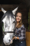 Western beauty with her horse. Girl in a plaid shirt with a horse in the stable stock images