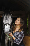 Western beauty with her horse. Girl in a plaid shirt with a horse in the stable royalty free stock photos