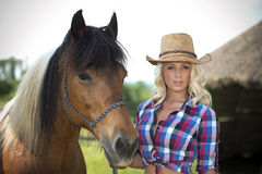 Western beauty with her horse. A beautiful western woman taking care of her horse stock image