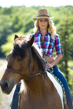 Western beauty on horse. A beautiful blonde woman with western style clothes riding on her horse Stock Image