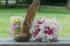 Western booth with bridal bouquet and rings. Old worn cowboy booth with wedding bouquet, ring set and jar of daisies Royalty Free Stock Photography