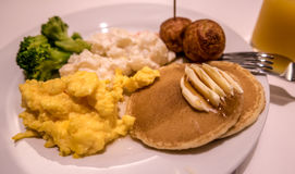 A western breakfast with a Japanese touch. A western breakfast made up of pancakes, omelette, potato salad, boiled broccoli, orange juice and the classic Royalty Free Stock Image