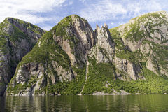 Western Brook Pond Cliff Wall. A huge animal-shaped rock formation stands amidst the cliffs above Western Brook Pond in Gros Morne National Park, Newfoundland Royalty Free Stock Images