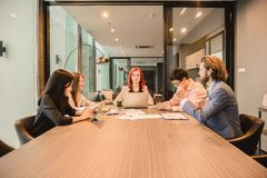 Western business woman boss meeting with her employees in meeting room and sharing ideas, , Multi ethnic royalty free stock image
