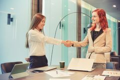 Western business women shaking hands in a meeting room, Multi et. Hnic Stock Photography