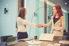 Western business women shaking hands in a meeting room, Multi et. Hnic Stock Image