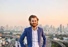 Western businessman smiling with blurry city background.  Stock Photography