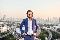 Western businessman smiling with blurry city background.  Royalty Free Stock Photos