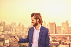 Western businessman using a phone on a rooftop with blurry city royalty free stock image