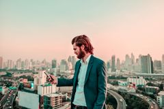 Western businessman using a phone on a rooftop with blurry city stock photography